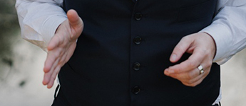 Matsui's hands in an engaged speaking position. One hand is opened the other is held naturally.