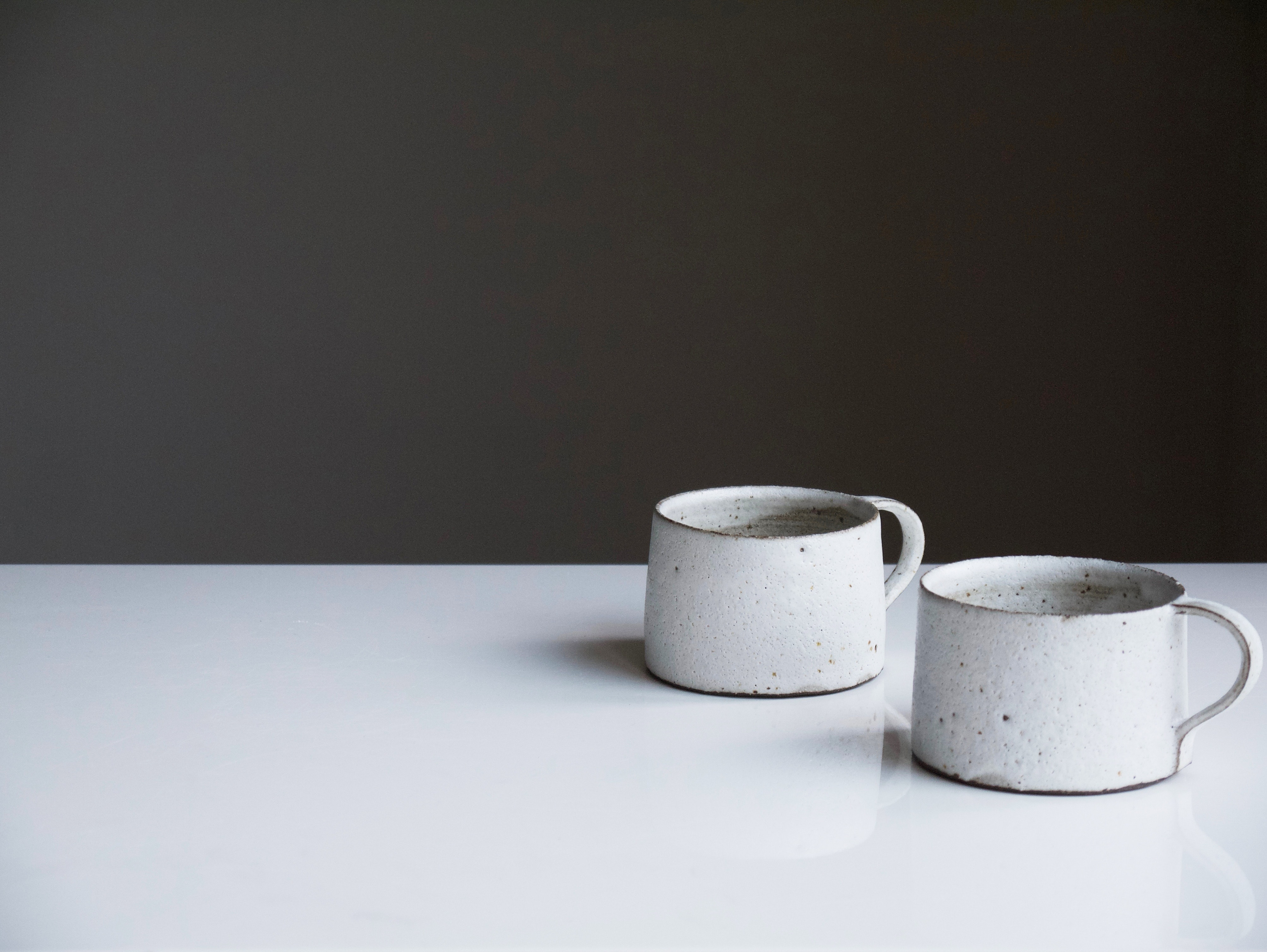 Two ceramic mugs sit on a white table